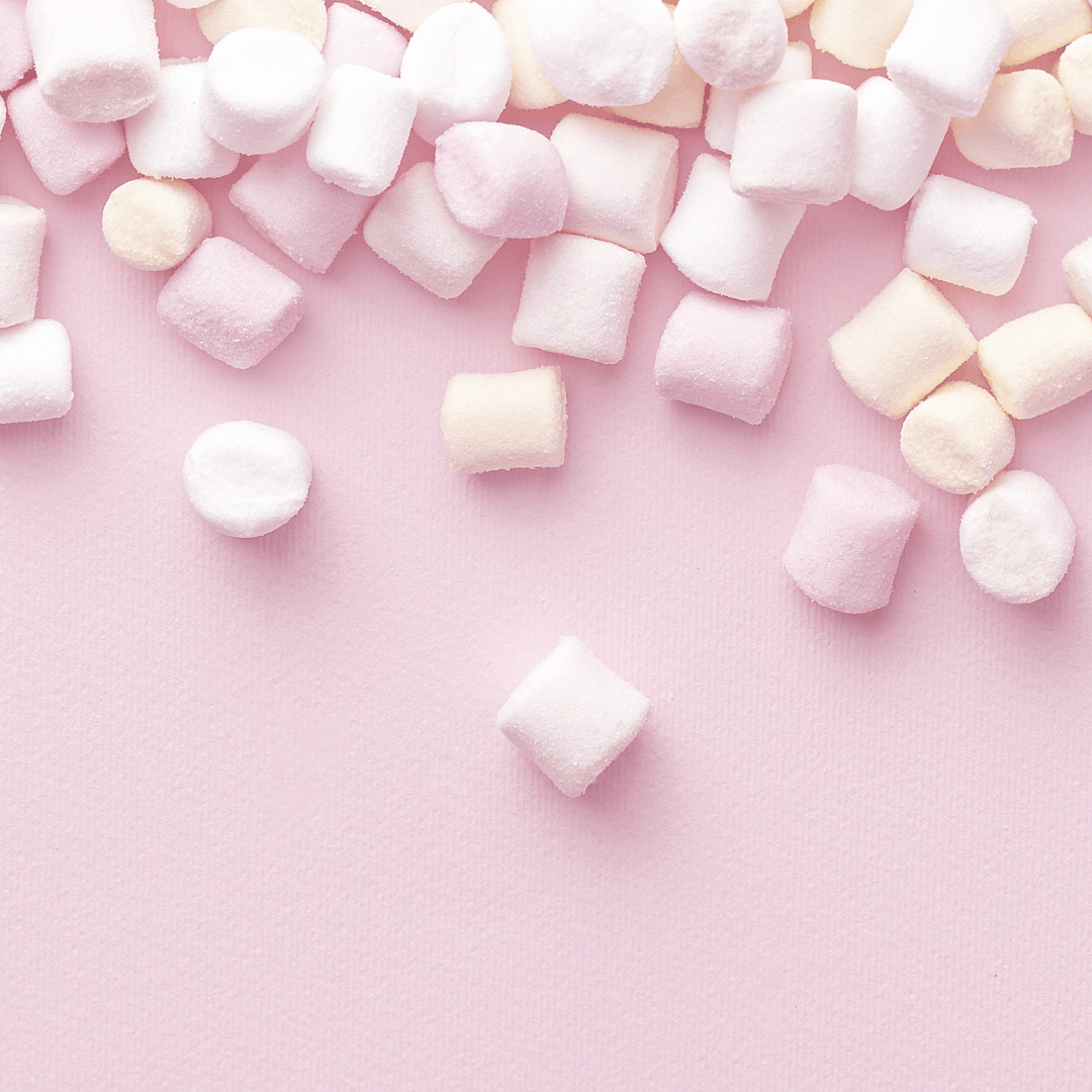 Marshmallows on a pink surface.